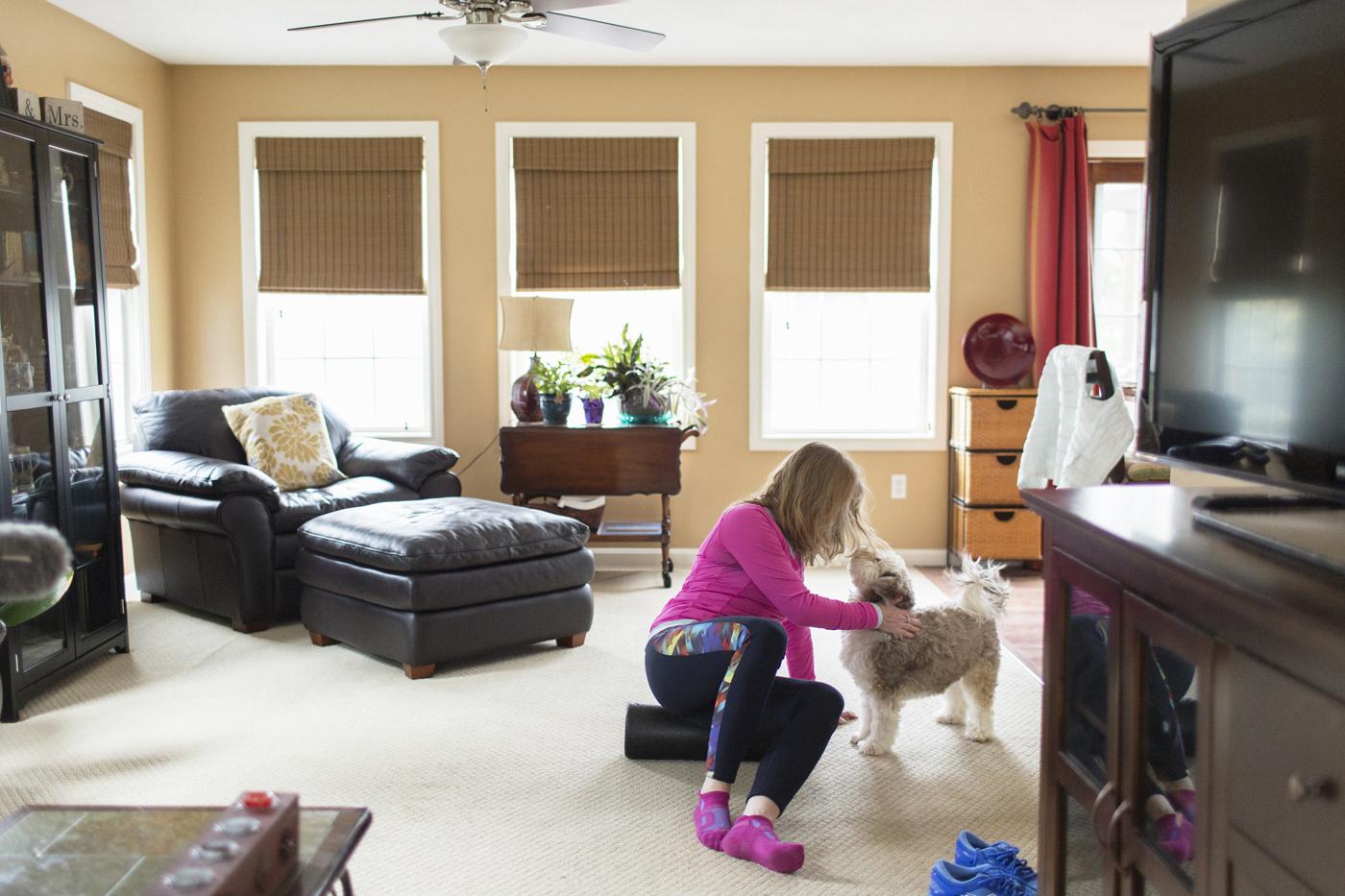 Faith inside her house, petting her dog.