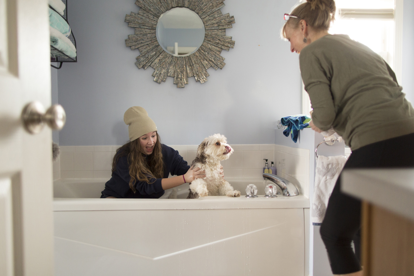 Faith watches as her daughter washes their dog.