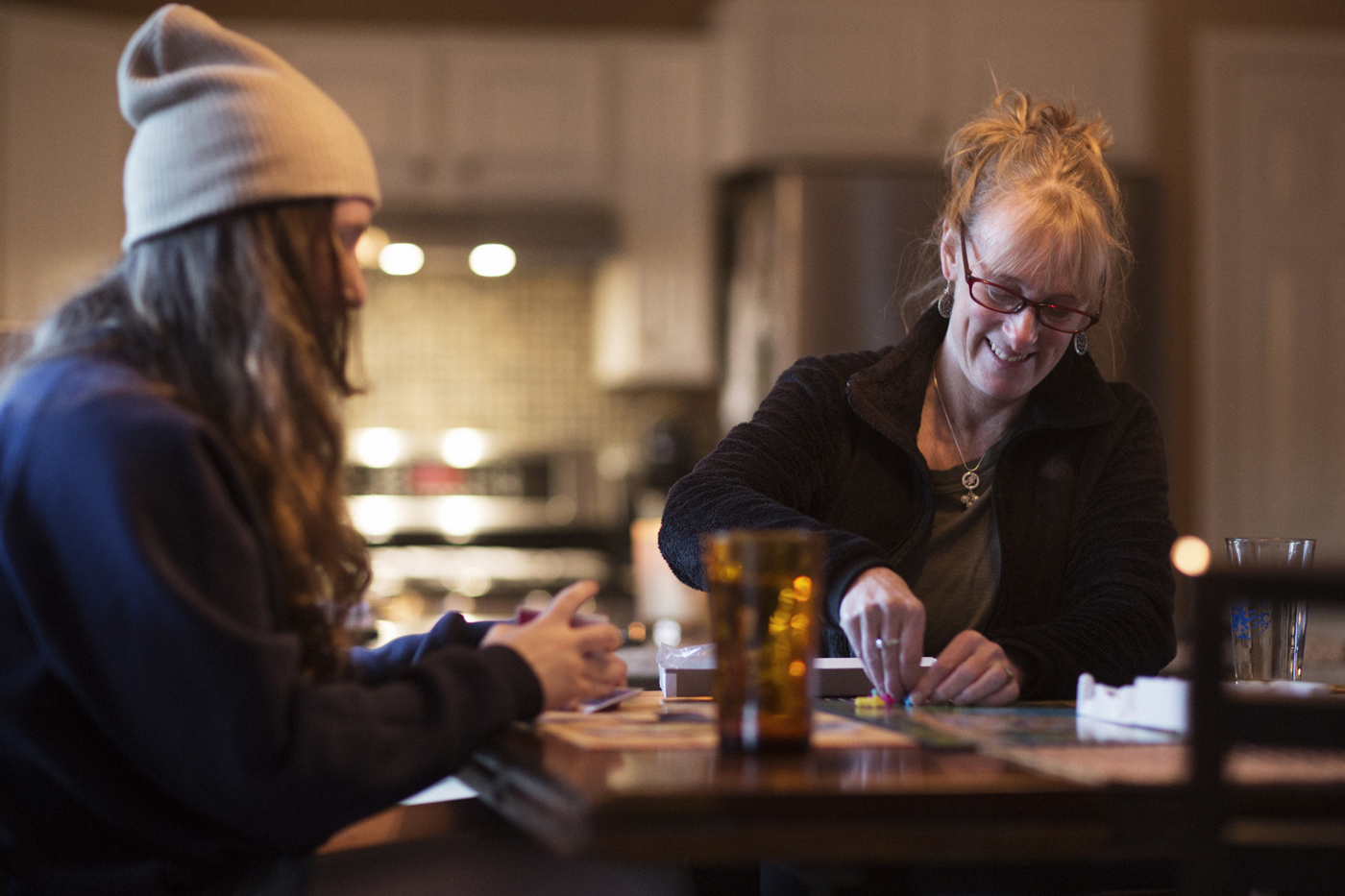 Faith and her daughter play a board game on the kitchen table.