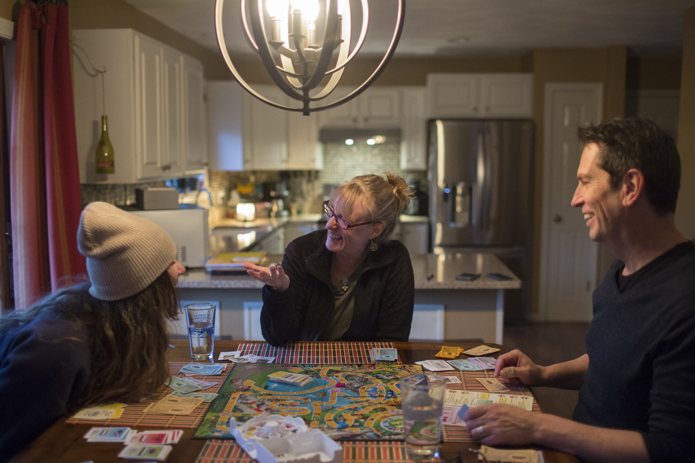 Faith, her daughter, and husband laugh as they play a board game in the kitchen.