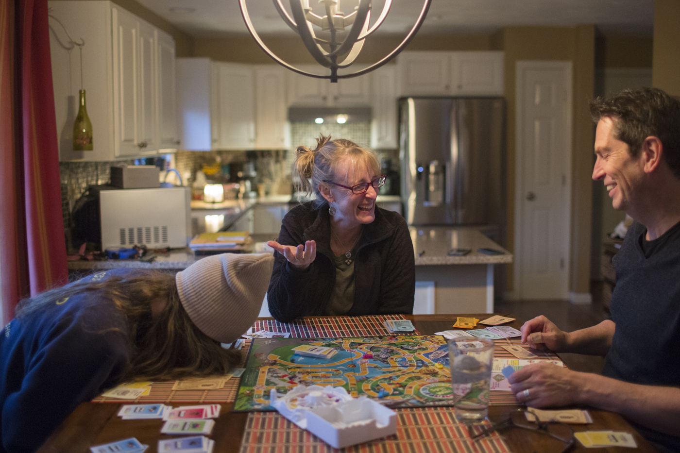 Faith's daughter doubles over with laughter as she plays a board game with her parents at the kitchen table.