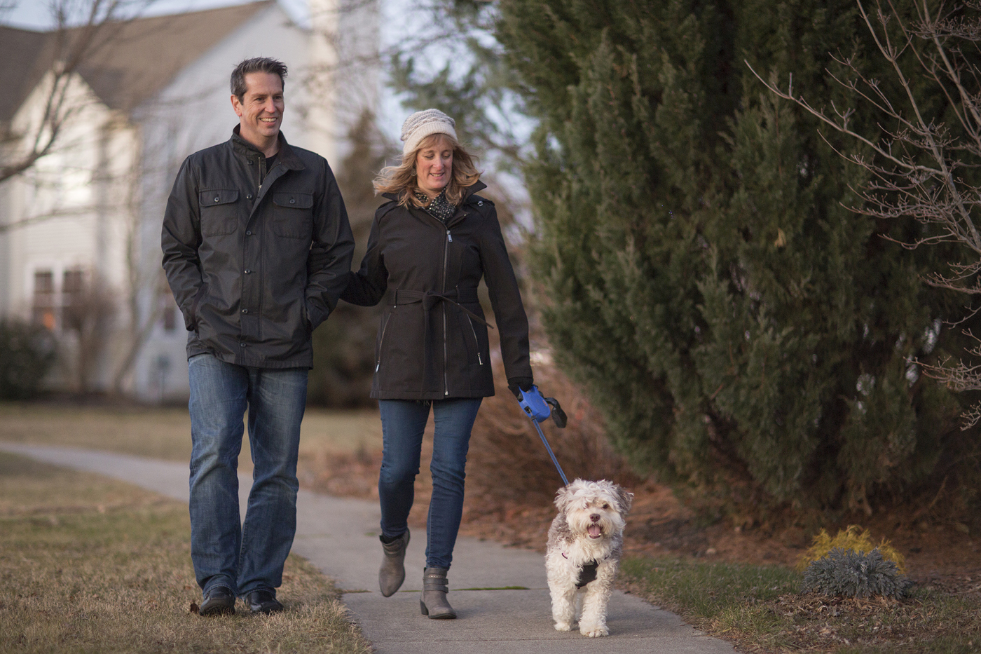 Faith and her husband walk outside with their dog.