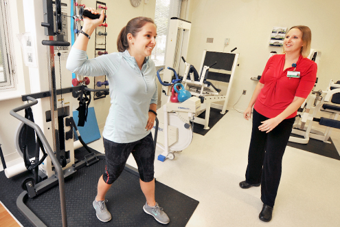 A patient exercises her arms as a rehabilitation therapist observes.