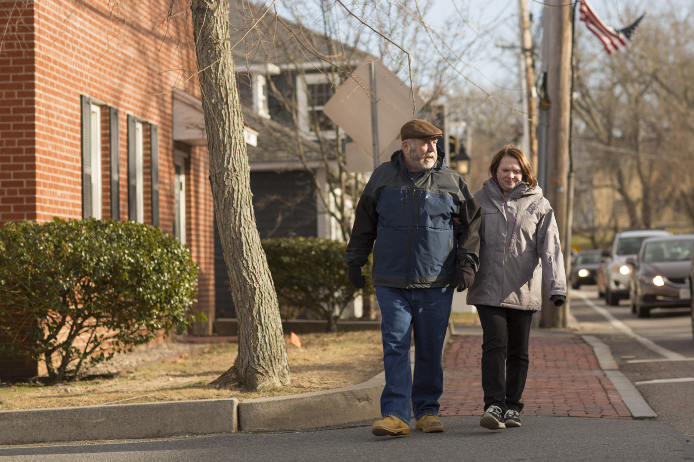 Ramona and her husband walk along a local town road.