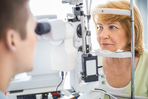 Doctor examines patient's eyes with machine.