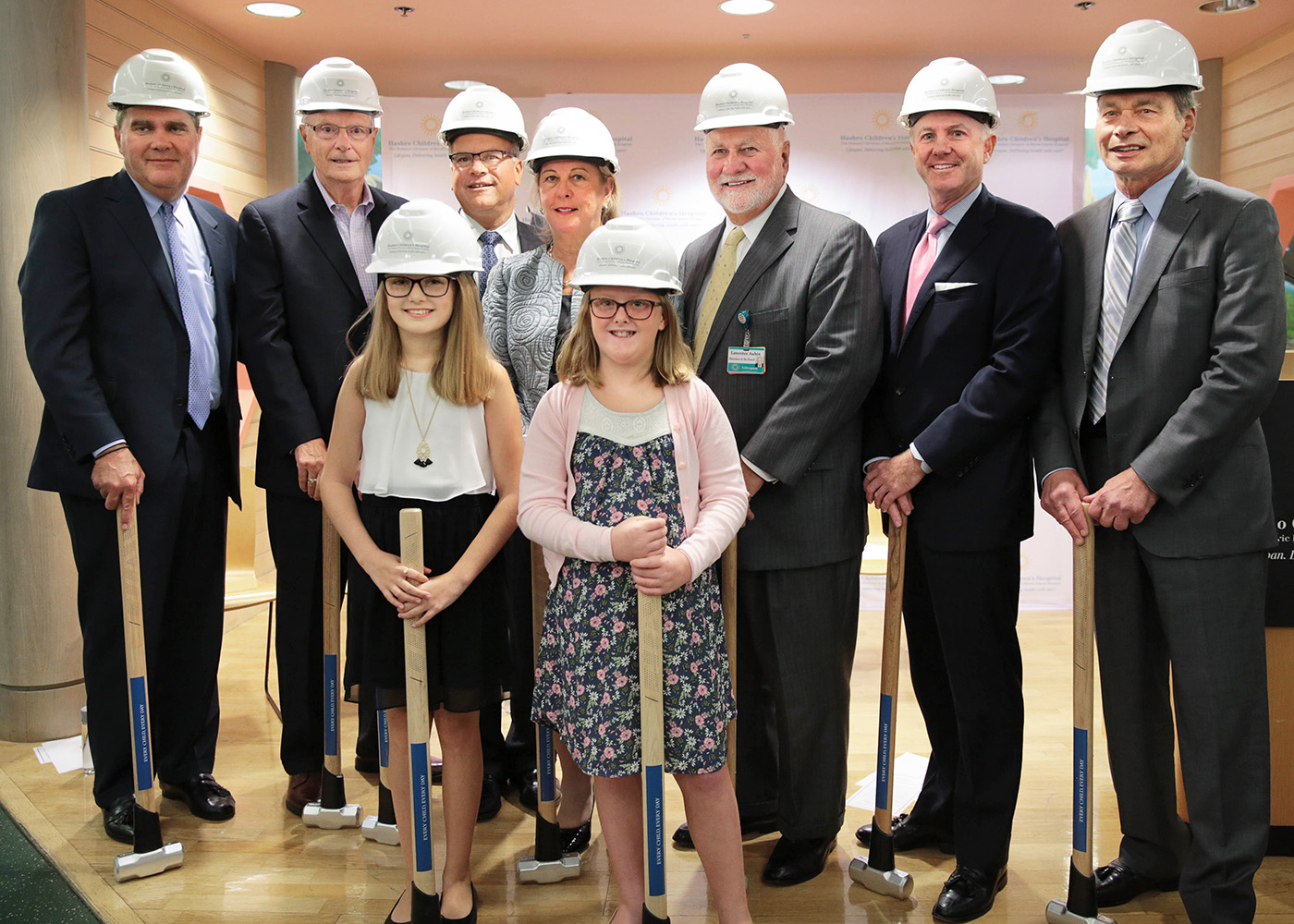 Lifespan, Hasbro and community leaders, along with essay winners, wearing hardhats for a symbolic groundbreaking