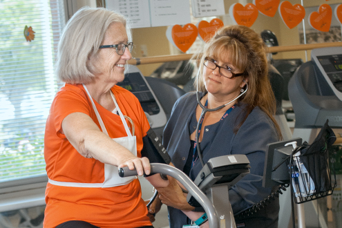 Resources and information for Lifespan cardiovascular patient on leg machine with physical therapist watching.