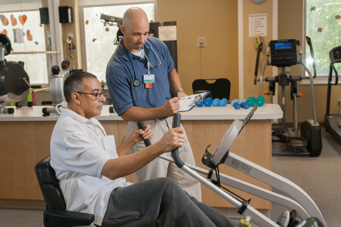 Physical therapist keeps track of patients progress on leg machine.