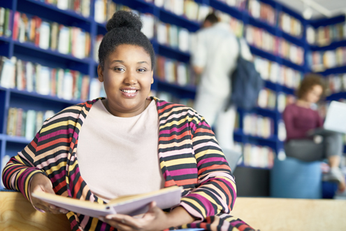 A smiling teenage girl sits in a library