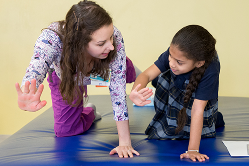 Children's Physical Therapist helping girl work out arm and leg.