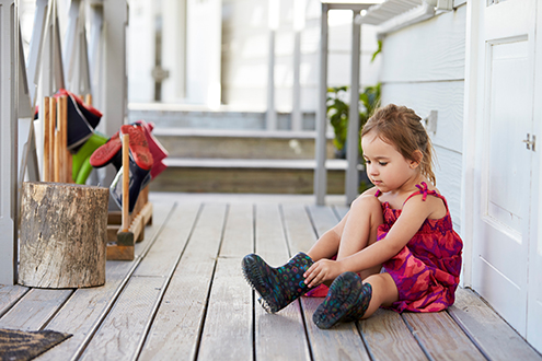A young girl sits on the porch of her house, putting on a boot.