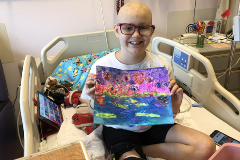 A patient displays the painting she created.