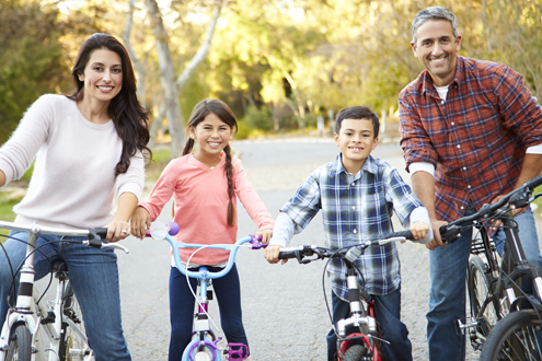 A family of four rides their bicycles.  Lifespan Community Health Institute.
