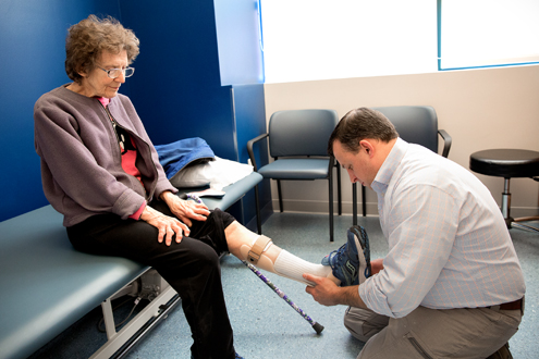 A patient's leg is examined by a member of Physical Medicine
