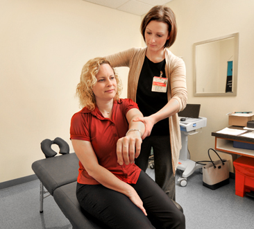 A chiropractor treats a patient's arm.