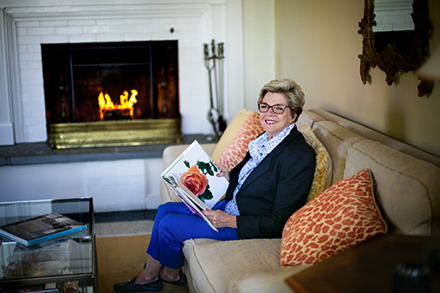 Cynthia O'Malley enjoys her fireplace as she sits on her couch.