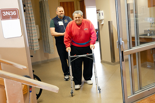 A smiling man uses a walker following hip surgery at the Lifespan Orthopedics Institute