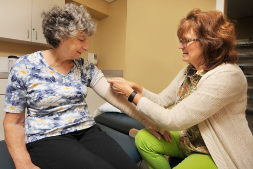 Physical Therapist wrapping patient's arm
