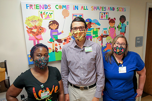 Three people from the pediatric endocrinology department stand in front of a piece of child's wall art.