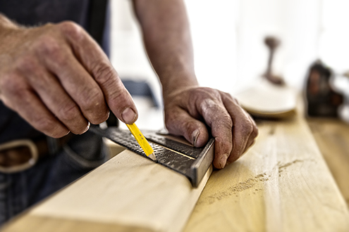 hands using a ruler cutting wood