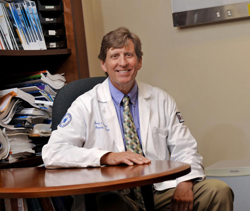 Damian Dupuy, MD sits at his desk with medical books on shelves behind him.