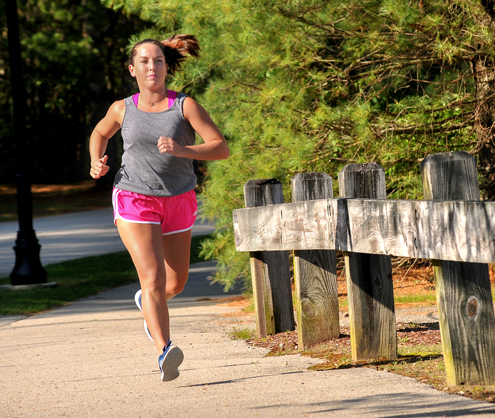 Brittney Lowe jogs along a tree-lined street.