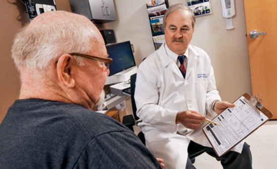Older male patient speaking with a doctor