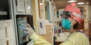 Lifespan health care worker in PPE entering data on a monitor