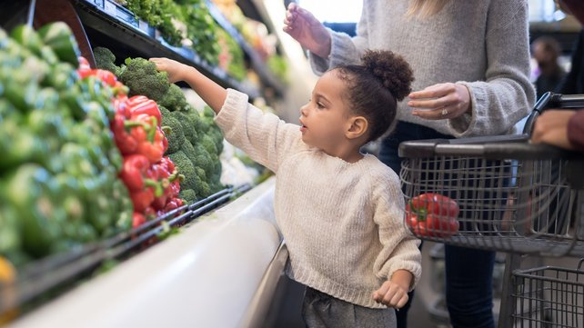 young child in grocery store picking out vegetables to put in shopping cart