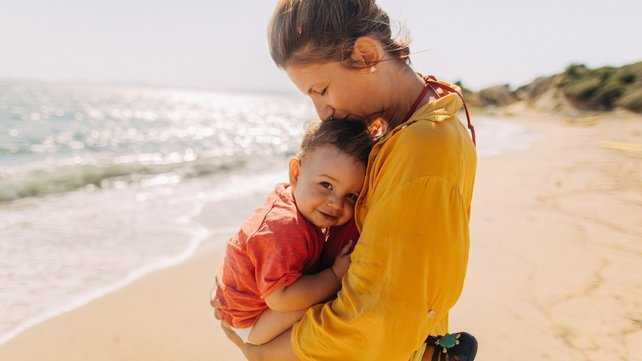 Woman holding and cuddling young child on beach