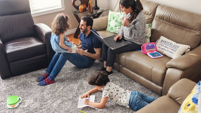 Mother and father spending family time with young son and daughter in living room