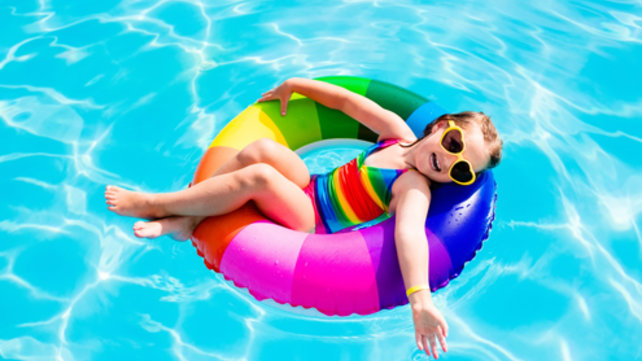 child in pool, floating on a rainbow float ring