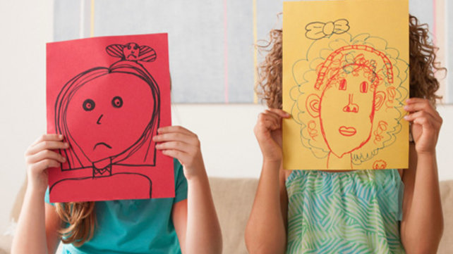 Children holding drawings in front of their faces