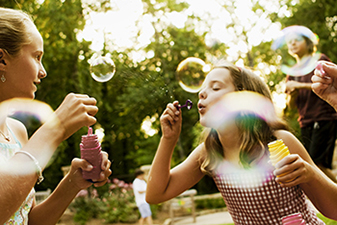 young girls blowing bubbles outside