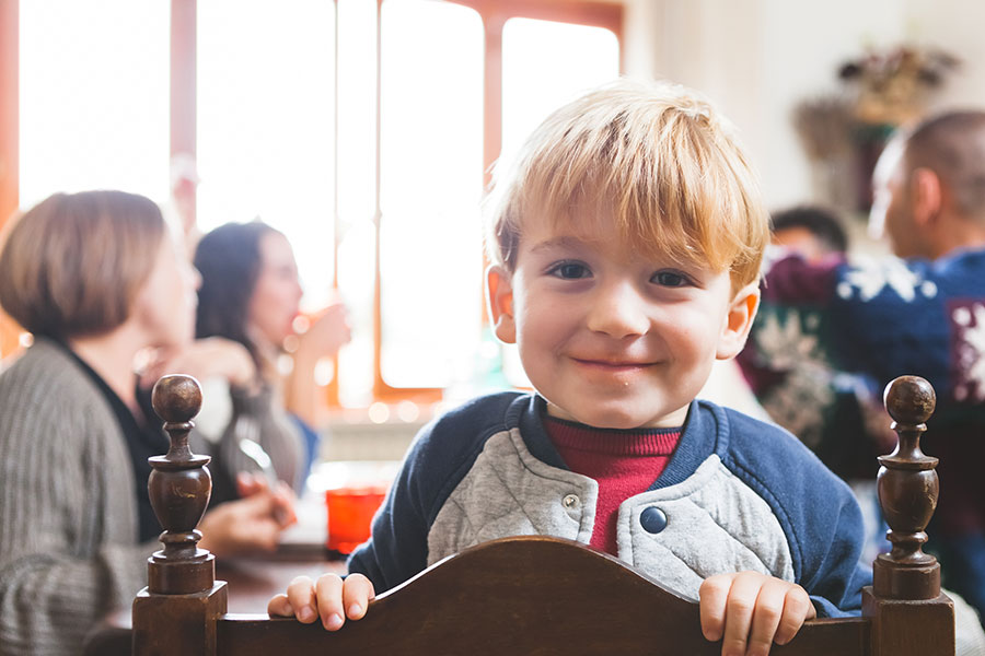 young boy smiling at table