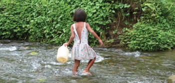young girl wading in stream
